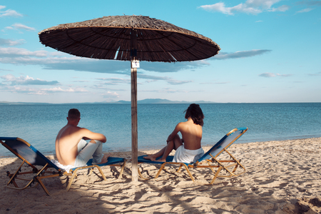 Couple in love with sexy body relax on beach. Summer holidays and paradise travel vacation. Love relations of naked couple at sea. Sexy woman and man suntan at umbrella. Family and valentines day