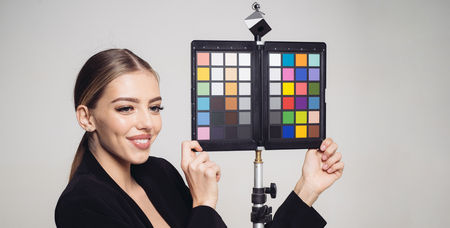 Blond girl holding color calibration charts isolated on gray background. Smiling assistant of photographer or cameraman helping to adjust color settings. Stock Photo