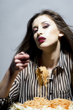 Gorgeous young brunette woman having italian food. Фото со стока