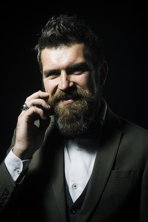 Happy man with beard and mustache on unshaven face. Bearded man smile with stylish hair. Fashion hipster wear bow tie with formal jacket. Skincare and grooming concept. Barber and hair salon. Stock Photo