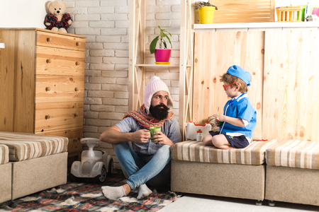 Father and son playing doctor at home. Dad with tea mug listening to kid dressed as nurse. Physician with serious face giving instructions to bearded man in denim outfit, medical treatment concept.