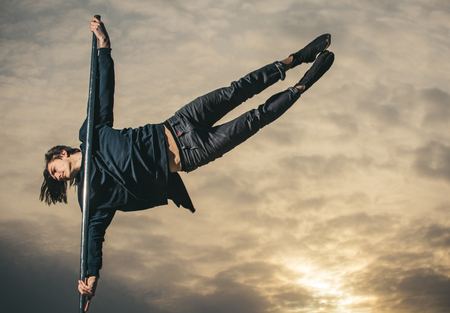 Athletic guy make acrobatic elements on pylon. Pole dance sport. Sexy macho man fly on sky background. Strong man dancer workout on pole in sunset. Young man dancing on pylon. Full of energy