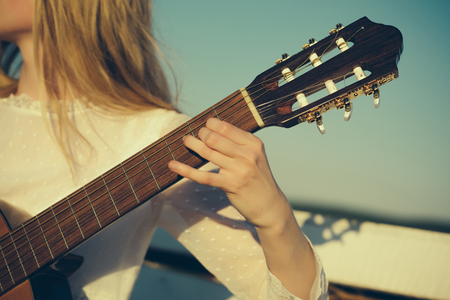 Guitar with fingers strumming strings. Hand play on string instrument. Classic guitar neck fretboard and headstock on sunny blue sky. Music and entertainment concept.