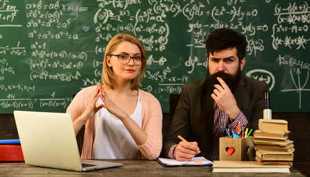 Modern teacher hipster writing on big blackboard with math formula, Speaker at university meeting in the conference classroom, Successful students are mostly creative,