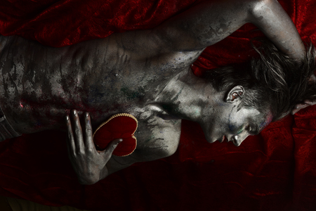 Valentines day concept. Macho on mysterious face with make up, covered with shimmering silver paint and colorful glitters. Man with nude torso holds red plush soft heart toy on chest, dark background.