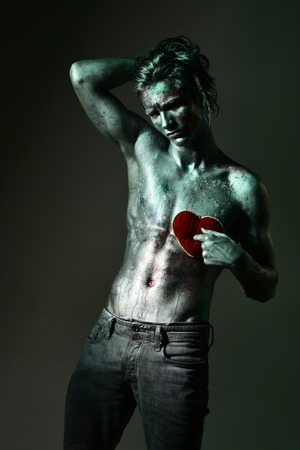 Man holds plush soft heart near his chest. Love, depression, disappointment, hurtful. Handsome man of athletic build, completely covered in silver paint and glitters on black background.