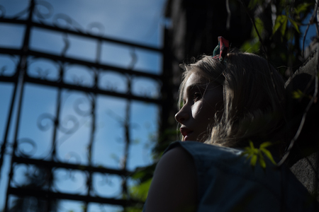 Side view frightened girl wearing headband standing behind tall gate at dusk. Pretty young lady with curled blond hair lost in park at night. Mysteries hidden by darkness.