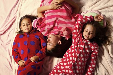 Girl friends in pajamas sleep in bed, top view