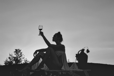 Sensual woman body. Silhouette of girl with wine