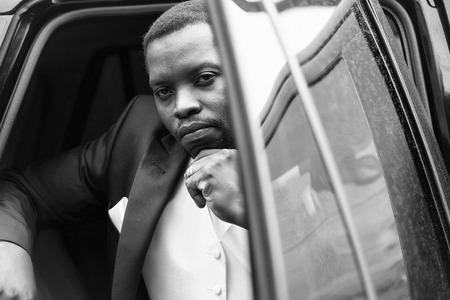 Man looking at camera. Handsome groom sits in car Stock fotó