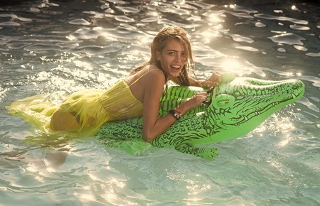 Sensual woman body. Adventures of girl on crocodile. Sexy woman on sea with inflatable mattress. Relax in luxury swimming pool. Summer vacation and travel to ocean, maldives. Fashion crocodile leather and girl in water Banco de Imagens