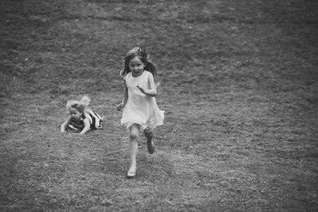 Child Childhood Children Happiness Concept. Kids run and fall on green grass on summer day