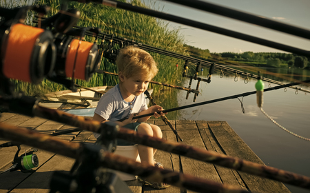 Kids playing - happy game. Adorable little boy fishing from wooden dock on lake
