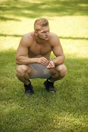 Man sit on green grass on sunny day