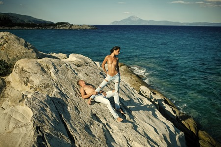 Couple secrets fantasy. Honeymoon concept. Sensual nude attractive couple on pensive faces. Sexy topless couple stands, lies on stone or reef in sea. Stock Photo - 101584739