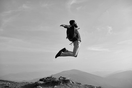 Man hipster jumps with backpack Standard-Bild - 101585428