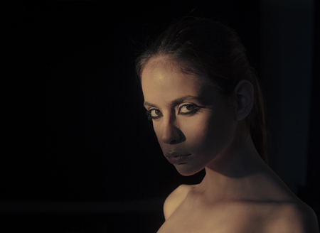 Girl with smokey eyes wearing her hair in a bun on the black background.