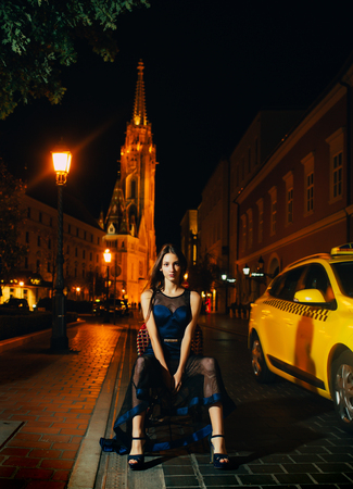 Luxury woman in evening dress at night city go to prom on taxi. Girl with glamour makeup. Night city with princess in celebrity style. Fashion and beauty of business lady. Sexy girl in elegant dress.