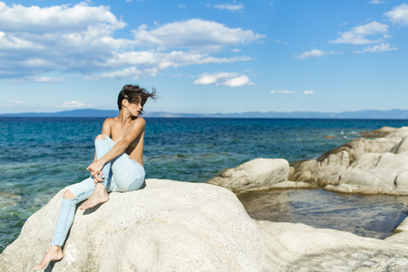 Sensual nude attractive girl on pensive face on windy day. Sexy topless lady sits on stone or reef in sea. Woman enjoy view and suntanning, sea surface background. Vacation and freedom concept. Stock Photo - 104444207