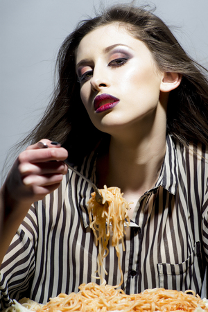 Young beautiful woman eating spaghetti on grey background.