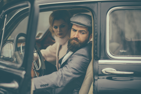 Travel and business trip or hitch hiking. Retro collection car and auto repair by mechanic driver. Couple in love on romantic date. Bearded man and sexy woman in fur coat. Escort of girl by security Stock fotó