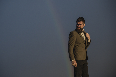 Bearded man gay and rainbow. Hipster with beard and mustache on grey sky. Fashion businessman in classic coat with bow tie. Vacation and wanderlust. Gender equality rights and freedom, copy space.