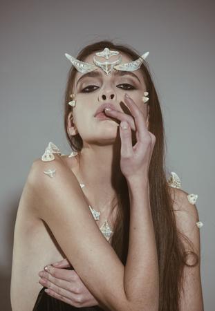 Woman with spikes on skin and horns on the head, Halloween costume, creative make-up.