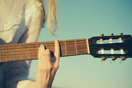 Concert hand play on guitar on sunny blue sky. Concert of classic guitar with strings. Stock Photo