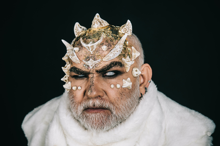 Demon with golden reptilian skin and beard wearing white fur, closeup. Man with fictional makeup on black background. Monster with white eyes and thorns on face, horror and fantasy concept.
