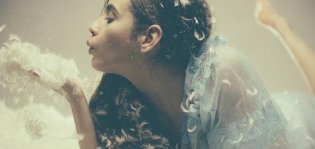 Encantadora chica en camisón azul vistas laterales aisladas sobre fondo beige. Foto de archivo