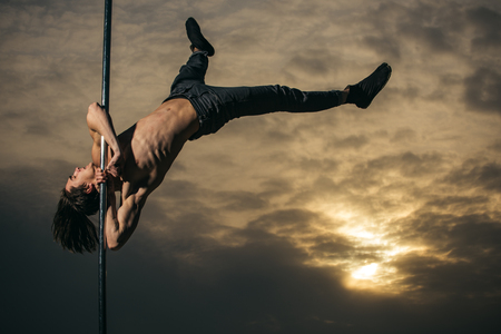 Pole dance sport. Young muscular man dancing on pylon in sunset. Athletic guy make acrobatic elements on pylon. Strong man dancer workout on pole. Sexy macho man fly on sky background.