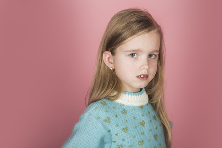 Kleines Mädchen mit langen Haaren. Friseur, Hautpflege, Casual Style, Denim. Stilvolles Mädchen mit hübschem Gesicht auf grauem Hintergrund. Schönheits- oder Kindermode mit Kosmetik und gesundem Haar.