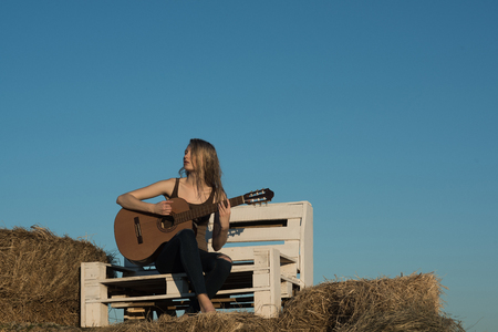 Music woman play guitar on wooden bench on blue sky. Music, woman guitarist perform concert on acoustic guitar Stock Photo