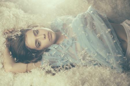 Jonge vrouw in blauwe zijden jurk liggend op een zachte stapel witte veren, fantasie voor het slapengaan. Tederheid en concept.