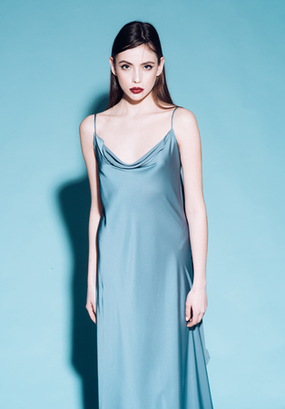 Beautiful girl in icy blue fluttering atlas dress isolated on blue background.