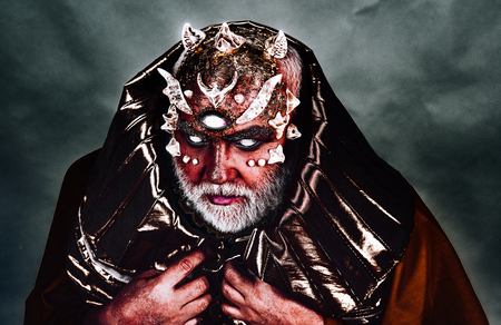 Demon with three eyes and red skin wearing metallic golden hood. Monster with sharp thorns on face, horror and fantasy concept. Devil raising from hell on black background, Halloween idea. Zdjęcie Seryjne