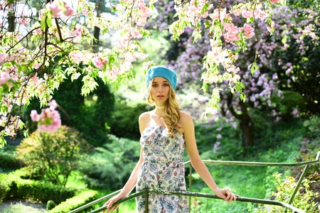 Charming girl in light strapless dress and blue beret hat standing on small bridge under blooming tree with pink fragrant flowers. Colorful impressionist picture in pastel tones of spring garden. Stock Photo