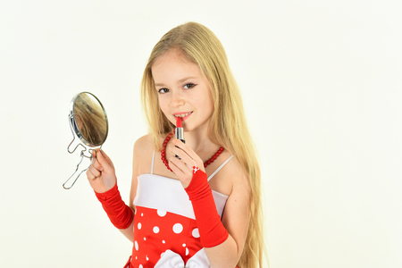 childhood and happiness. childhood, little girl pit red lipstick on lips with mirror Stok Fotoğraf