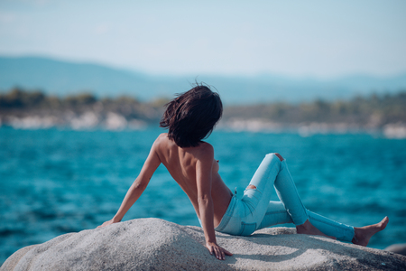 Sexy woman topless in jeans. naked woman at sea water on stone. sexy body of girl relax on beach. Fashion and beauty concept. Summer holidays and paradise travel vacation Banque d'images
