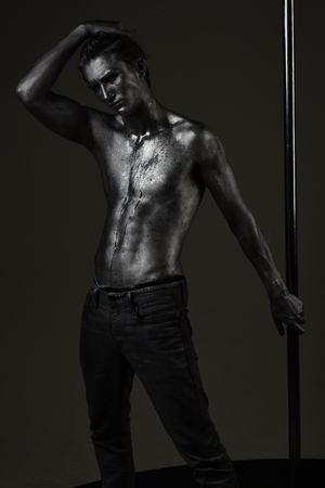 Macho with naked chest, athlete, sportsman hold metallic pole. Fashion shot of young sexy mysterious athlete. Man with nude torso covered with shimmering silver paint, dark background. Fashion concept