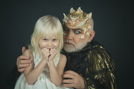 Little blond smiling angel in white outfit embraced by monster with dragon skin and thorns. Good vs evil, fantasy, innocence of childhood. Bearded man with alien, demonic make-up on black background.