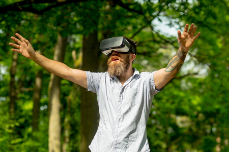 Man with open mouth and beard in VR glasses walking in forest, technologies concept. Hipster with long beard and tattoo on natural background. Bearded man exploring surroundings with top-notch gadget.