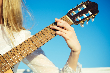 Classic guitar neck fretboard and headstock on sunny blue sky. Guitar with fingers strumming strings. Hand play on string instrument. Music and entertainment concept.