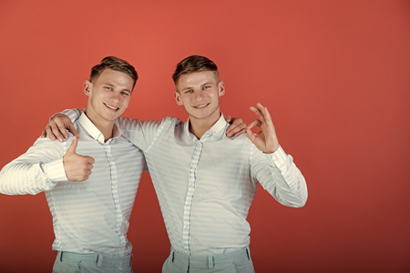 Two brothers showing thumbs up and ok gestures