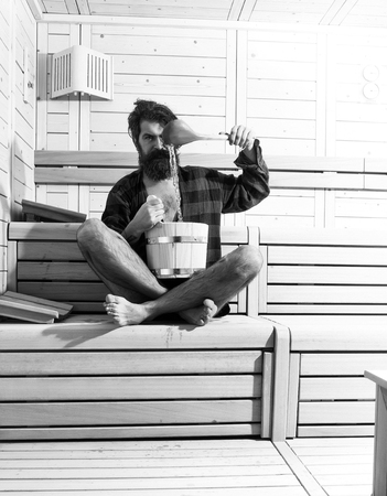 Mens heals body care. handsome bearded man in wooden bath with bucket and spoon Фото со стока