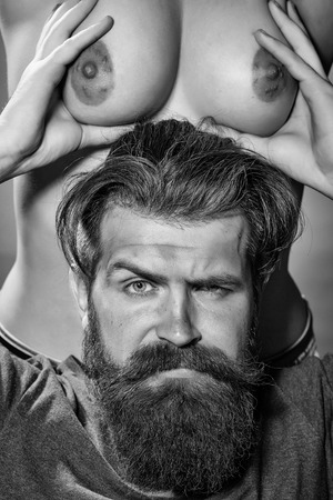 man with serious emotion. Bearded man and female chest