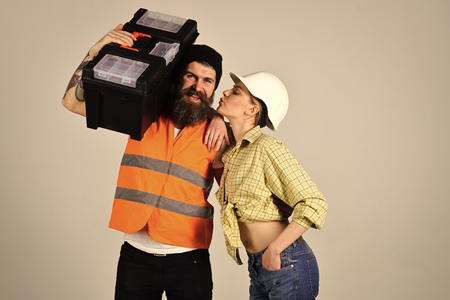 Man looking at camera. Housewife flirting with repairman with toolbox. Girl with helmet on kissing face near strong man with beard Stock Photo