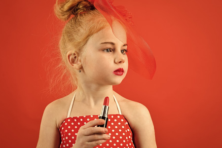Child Childhood Children Happiness Concept. Retro girl fashion with cosmetics, beauty. Little girl hold lipstick and mirror. Fashion and beauty, pinup style, childhood. Child girl in stylish dress, makeup. Makeup retro look and hairdresser