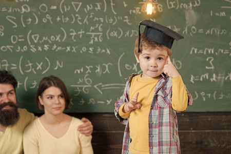 Happy kid having fun. Wunderkind concept. Smart child, wunderkind in graduate cap pointing at his head. Boy presenting his knowledge to mom and dad. Parents listening their son, chalkboard on background.