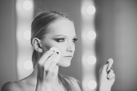 High fashion portrait of elegant woman. Woman using cotton pad on face for makeup removal Imagens